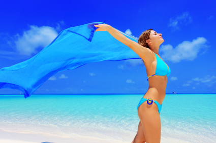 Happy woman walking on a beach with long sarong.