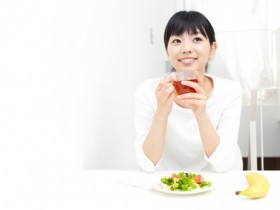 a young asian woman eating salad