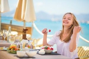 Young woman eating fruits in a beach restaurant